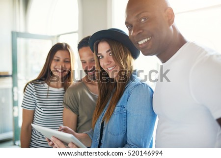 Young trendy smiling group of four friends with tablet having fun and looking at camera in sunlight.