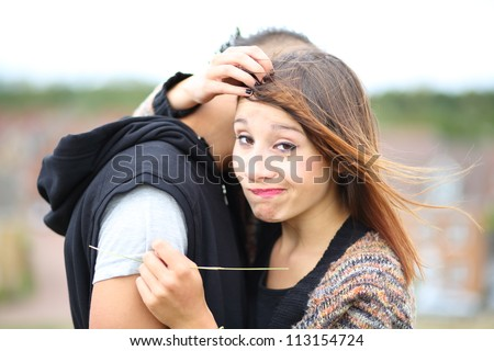 Young trendy urban couple. Pretty girl with brown hair and piercing brown eyes looking into camera, making a funny face, in embrace with boyfriend with Mohawk hairstyle and hoodie. - stock photo