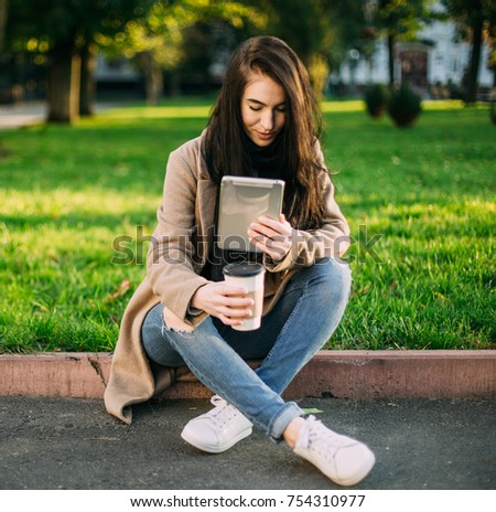 young trendy woman in autumn city park with smartphone in hand