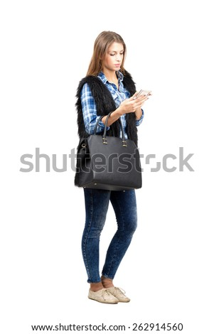 Young trendy woman typing on the smartphone. Full body length portrait isolated over white background - stock photo