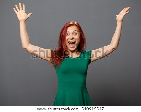 Young triumphed woman in a green dress with the hands up, gray background