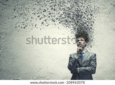 Young troubled businessman thinking over the ideas - stock photo