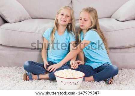 Young twins eating popcorn sitting on a carpet in the living room