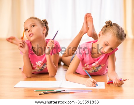 Young twins sisters are drawing on paper with colored pencils lying on the floor. - stock photo