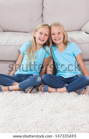 Young twins sitting on a carpet in the living room