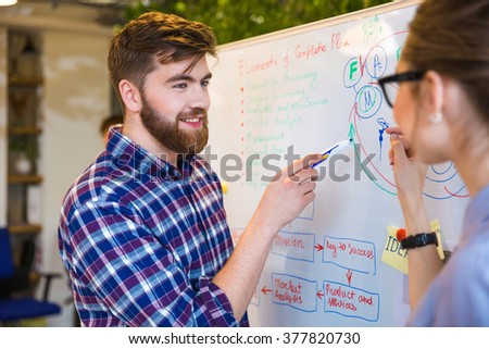 Young two people discussing about business plan in office - stock photo