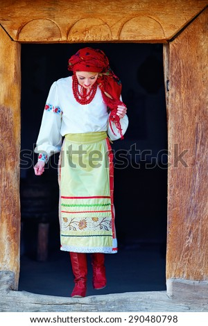 young ukrainian girl, dressed in national costume, walking out from house - stock photo