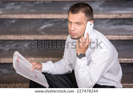 Young unemployed man is looking for a job in the newspaper,  and phone, sitting on the stairs. - stock photo