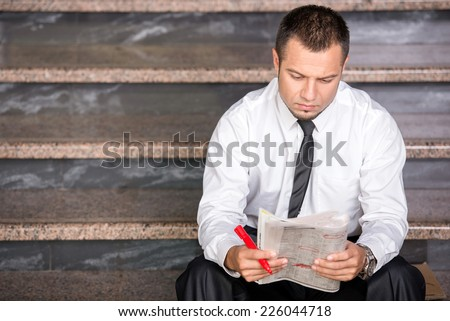 Young unemployed man is looking for a job in the newspaper, sitting on the stairs. - stock photo