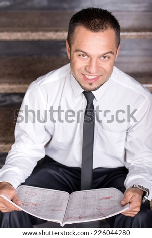 Young unemployed man is looking for a job in the newspaper, sitting on the stairs. Looking at the camera.