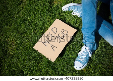"Young unemployed man lookig for a job with ""Need a job"" cardboard - stock photo"