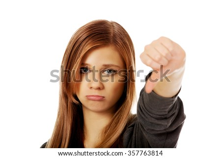 Young unhappy teenage woman showing thumb down. - stock photo