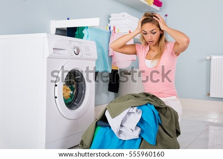 Young Unhappy Woman Looking At Pile Of Dirty Clothes Near Washing Machine At Laundry Room
