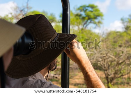 Young unidentified couple on safari in a jeep and looking through binoculars / using their camera
