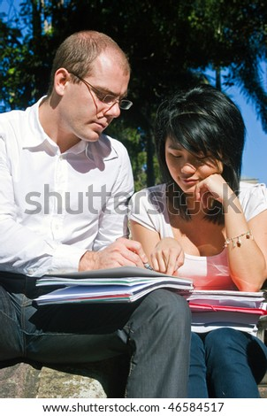 Young university professor explaining something to one of his students on a beautiful day - stock photo