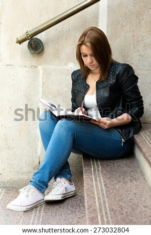 Young university student  girl preparing for the class by going over her homework sitting on the stairs of the campus - stock photo