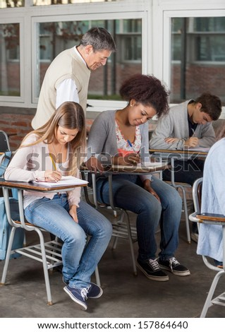 Young university students writing exam while professor supervising them in classroom - stock photo