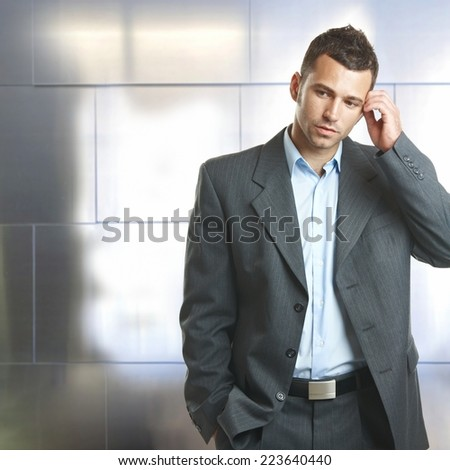 Young unsure caucasian businessman in suit standing and thinking in front of business office wall. Scratching head, wondering, hand in pocket. Copyspace, indoor. - stock photo