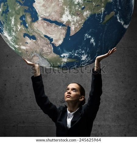 Young upset businesswoman holding Earth planet above head. Elements of this image are furnished by NASA - stock photo