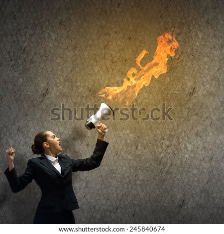 Young upset businesswoman screaming furiously in megaphone - stock photo