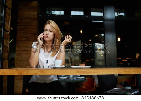 Young upset woman student talking on mobile phone while relaxing in cafe after lectures in University, concerned female have a bad conversation on cell telephone while sitting alone in coffee shop  - stock photo