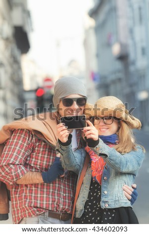 Young urban couple doing selfie outdoors.