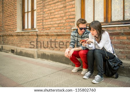 Young urban couple sharing information in the city - stock photo