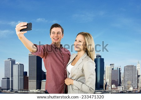 Young urban couple taking a selfie in front of the New York City Skyline                                 - stock photo
