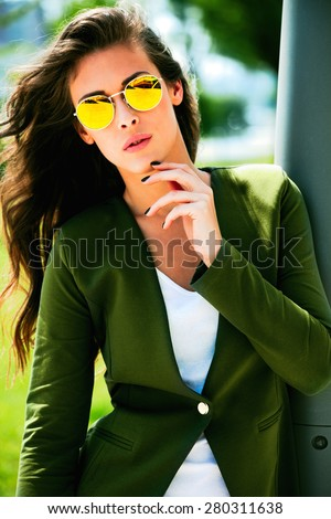 young urban fashion woman wearing yellow sunglasses and green jacket, outdoor shot in the city - stock photo