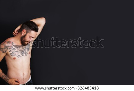 Young urban man with tattoos stripped to the waist in front of black background