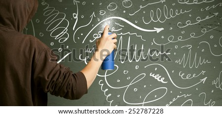 Young urban painter drawing curly lines and arrows on the wall