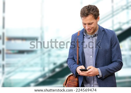 Young urban professional man using smart phone in office building indoors. Businessman holding mobile smartphone using app texting sms message wearing suit jacket and bag. - stock photo