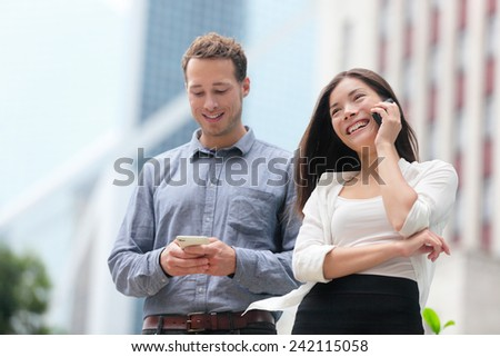 Young urban professionals business people on smartphones in Hong Kong. Businessman using app on smartphone and businesswoman talking having conversation on smart phone in Hong Kong Central. - stock photo