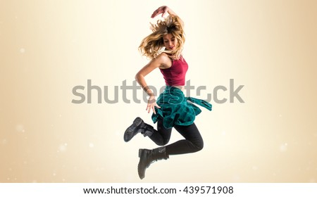 Young urban woman dancing over ocher background - stock photo