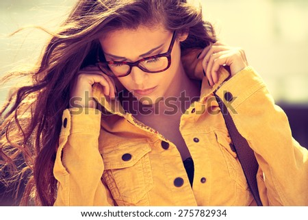 young urban woman with eyeglasses portrait,  outdoor shot in the city, retro colors - stock photo