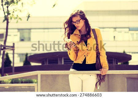 young urban woman with eyeglasses using smartphone,  outdoor shot in the city, retro colors
