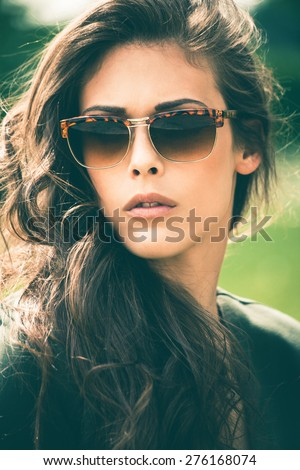 young  urban woman with sunglasses in the park portrait - stock photo