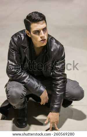 Young Vampire Man with Black Leather JacketPortrait of a Young Vampire Man with Black Leather Jacket Sitting on Floor - stock photo
