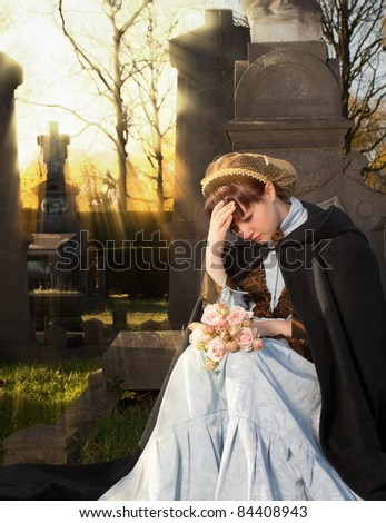 Young Victorian widow mourning on a tombstone at Halloween - stock photo