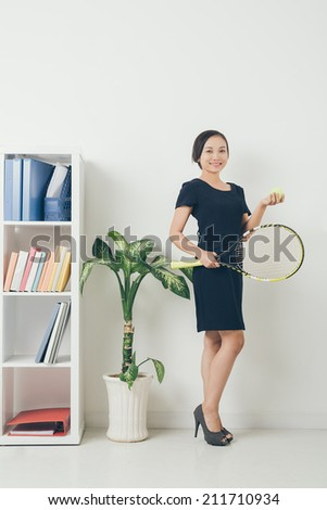 Young Vietnamese business lady holding tennis racket and ball - stock photo