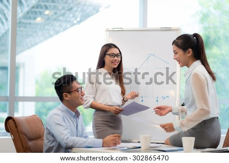 Young Vietnamese business team discussing chart on a whiteboard - stock photo