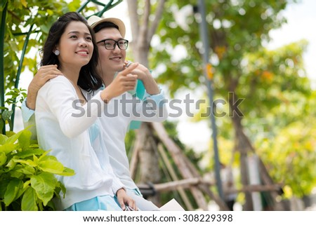 Young Vietnamese couple having date in the park - stock photo