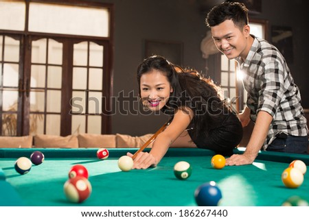 Young Vietnamese couple playing pool in the bar - stock photo