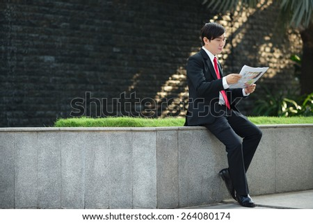Young Vietnamese managers sitting on parapet and reading daily newspaper - stock photo