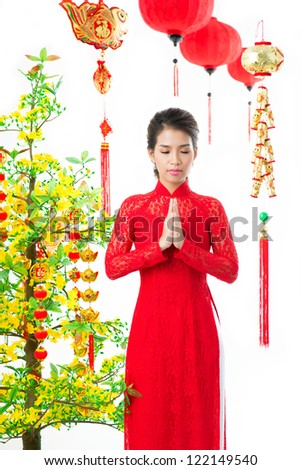 Young Vietnamese praying at apricot tree on traditional celebration - stock photo