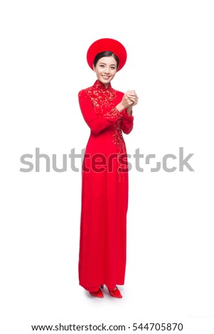 Young vietnamese woman in Ao Dai Dress with praying gesture wishing you good luck