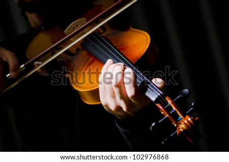 Young violin player playing - stock photo