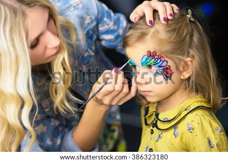 Young visagist painting the face of a little girl - stock photo