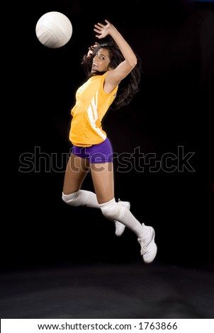 young volleyball girl in mid spike pose - stock photo