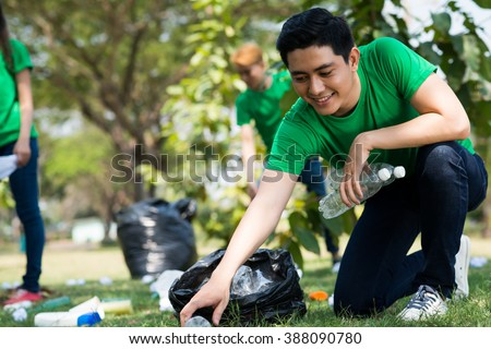 Young volunteer picking up plastic bottles in the park - stock photo